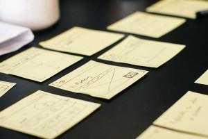 Image de post-it bien griffonné ordonnés sur une table noire.
