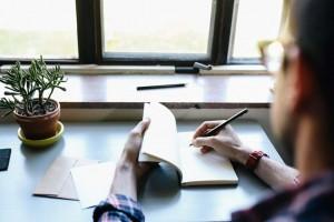 Quelqu'un assis à un bureau s'attache à noter quelque chose sur un papier.